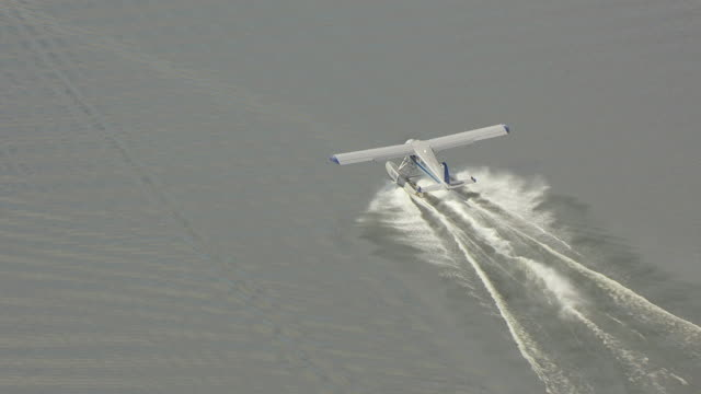 MS AERIAL TS Shot over float airplane driving in water at Lake Hood Seaplane Base / Anchorage, Alaska, United States