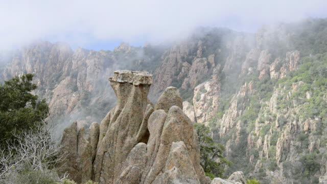 ms ha shot over fog moves over fantastic rocks of calanche of piana, unesco world heritage site / porto, corsica, france - ピアナ点の映像素材/bロール
