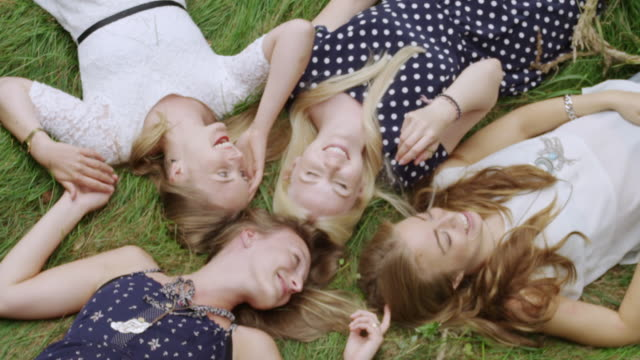 """ms slo mo shot over four women laying in grass on summer day laughing and playing / berlin, germany"" - four people stock videos & royalty-free footage"