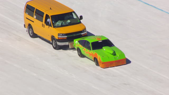cu aerial ts shot over green orange car taking off and racing at bonneville salt flats during speed week / utah, united states - bonneville salt flats stock videos and b-roll footage