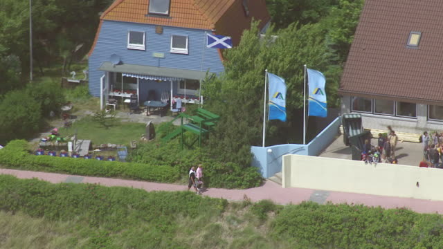 ms aerial shot over group of people at outside of hotel / amrum, schleswig holstein - nordfriesische inseln stock-videos und b-roll-filmmaterial