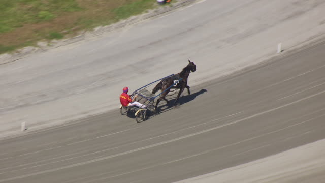 MS AERIAL TS Shot over harness racer running around Freehold raceway / Freehold Borough, New Jersey, United States