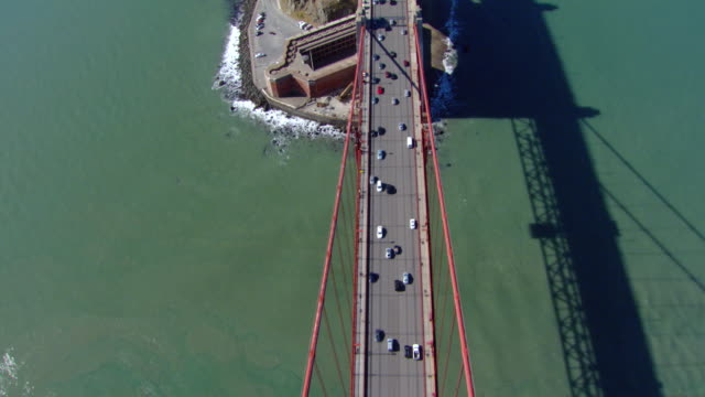 MS TS AERIAL Shot Over head approaching across Golden Gate Bridge with vehicles running / San Francisco, California, United States