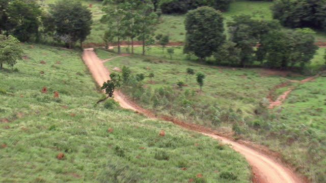 ms aerial pan shot over landscape and dirt road / minas gerais, brazil - minas stock videos and b-roll footage