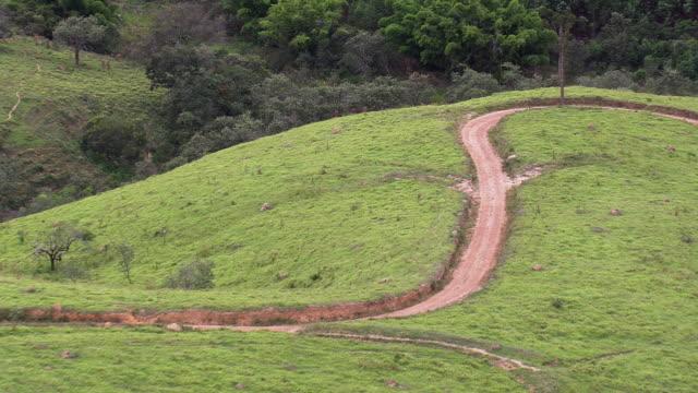 vídeos de stock, filmes e b-roll de ms aerial shot over landscape and dirt road / minas gerais, brazil - estrada rural