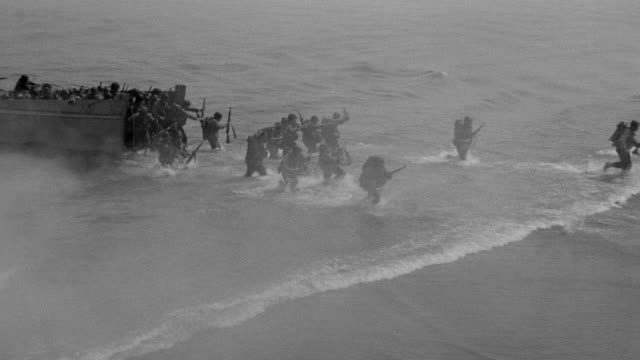 ws shot over ocean as troops running out from shore - military invasion stock videos and b-roll footage