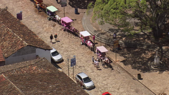 ms aerial shot over people, cars and horse cart / minas, gerais brazil - minas stock videos and b-roll footage