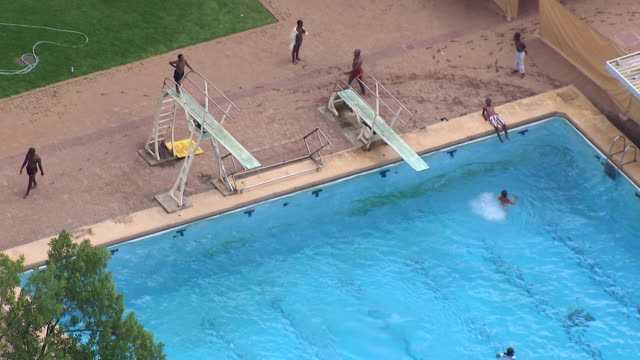 MS AERIAL Shot over people swimming in large swimming pool / Bloemfontein, Free State, South Africa