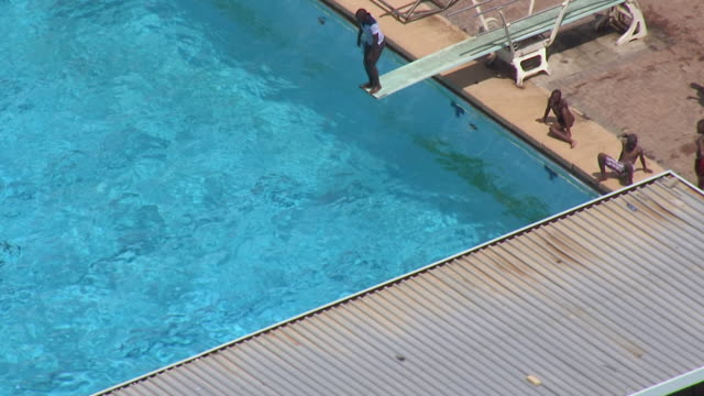 MS AERIAL Shot over people swimming in swimming pool / Bloemfontein, Free State, South Africa