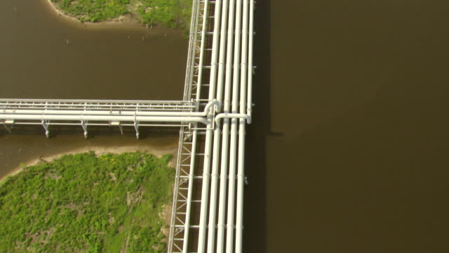 ms aerial shot over pipes at louisiana offshore oil port / louisiana, united states - pipe tube stock videos & royalty-free footage