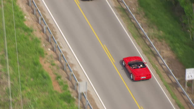 ms aerial ts shot over red corvette driving on road / bowling green, kentucky, united states - red convertible stock videos & royalty-free footage