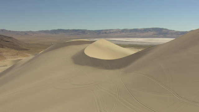 ms aerial shot over ridge of sand dunes at sand mountain in churchill county with mountains / nevada, united states - sand dune stock videos and b-roll footage