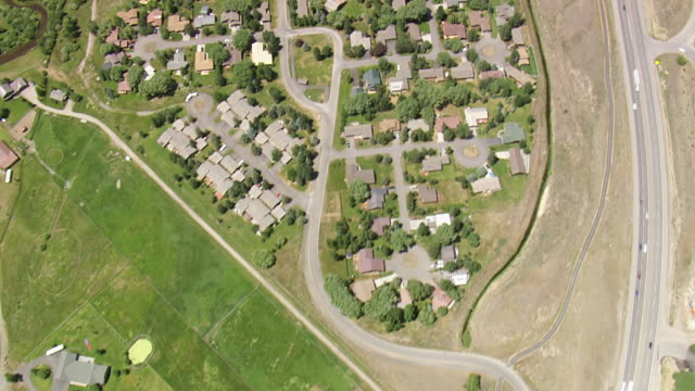 WS AERIAL Shot over roof tops of houses and road at South park / Wyoming, United States