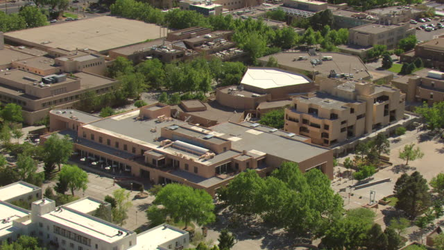 MS AERIAL Shot over University of New Mexico campus with pueblo style campus buildings / Albuquerque, New Mexico, United States