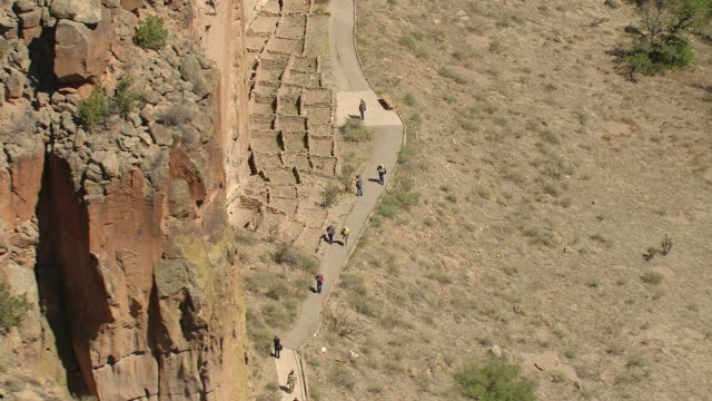 vídeos y material grabado en eventos de stock de ms aerial shot over visitors walking by ruins at bandelier national monument / new mexico, united states - vivienda en roca