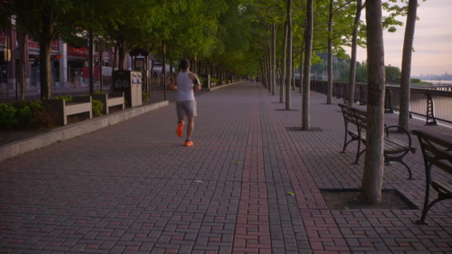 Shot pans from Manhattan Skyline to reveal people running along a path near the Hudson River in Hoboken