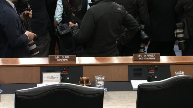 Shot sequence includes news media audience nameplates behind the dais entrance and reporters before the Senate Intelligence Committee convenes to...