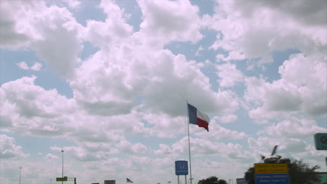 pov shot showing a texan flag flying next to a houston road, usa. - major road stock videos & royalty-free footage