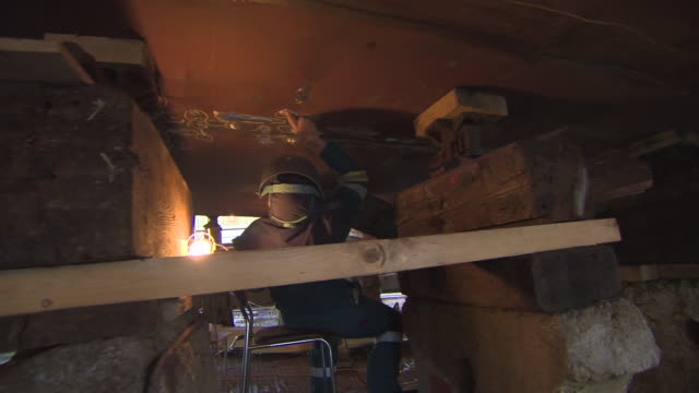 pov shot showing a walk underneath a ship in a shipyard where repair work is being carried out glasgow scotland fkaz191x clip taken from programme... - 造船所の労働者点の映像素材/bロール