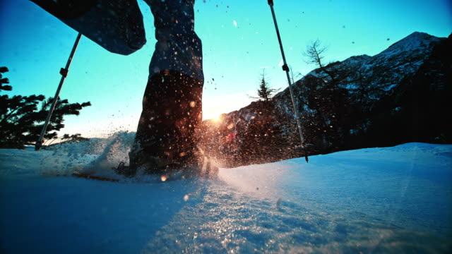 SLO MO LD shot Snowshoeing into sunset on mountain top