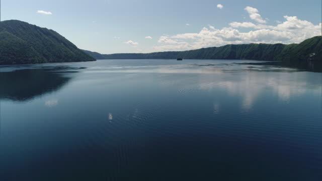 Shot taken by drone; Long shot of the surface of Lake Mashu, Hokkaido, Japan.