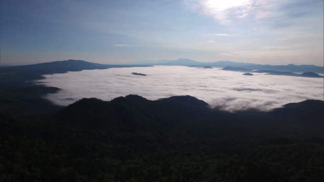shot taken by drone; pass over woods, look up to get a long shot of the sea of clouds over lake kussharo - stratus stock videos & royalty-free footage