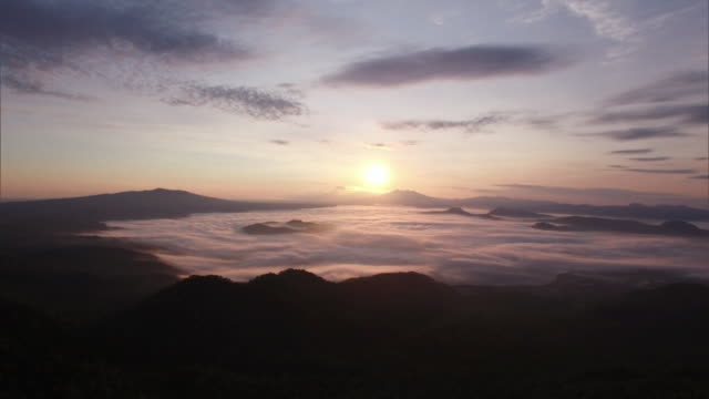 shot taken by drone; the sea of clouds over lake kussharo lit up in orange by the sun just after sunrise - hokkaido stock videos & royalty-free footage