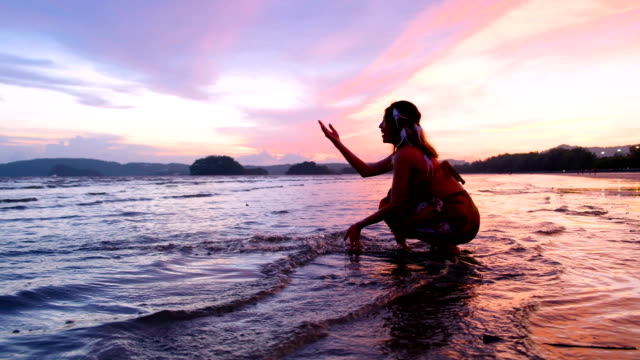 4k shot : teenage woman scoop up water with hands at seaside. relaxation on vacation. beautiful seascape at ko phangan island in thailand - ko phangan stock videos and b-roll footage