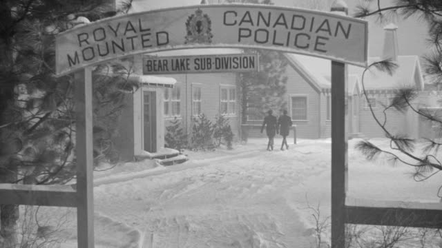 vídeos de stock, filmes e b-roll de ms shot through the gateway to royal canadian mounted police station, snow on ground, officers on foot and others drive in ground  - cultura canadense