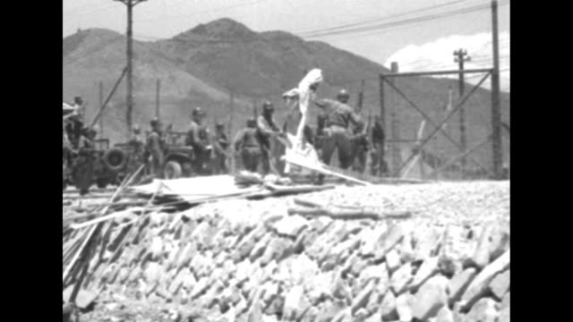 shot through wire fence of soldiers wearing gas masks rushing forward inside compound, one spraying banner set up by north korean communist prisoners... - communist flag stock videos & royalty-free footage