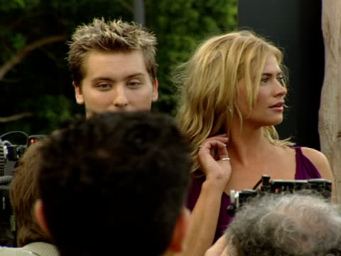 shot thru ots of paparazzi as they take pictures of lance bass and kristy swanson moving along red carpet - lance bass stock videos and b-roll footage