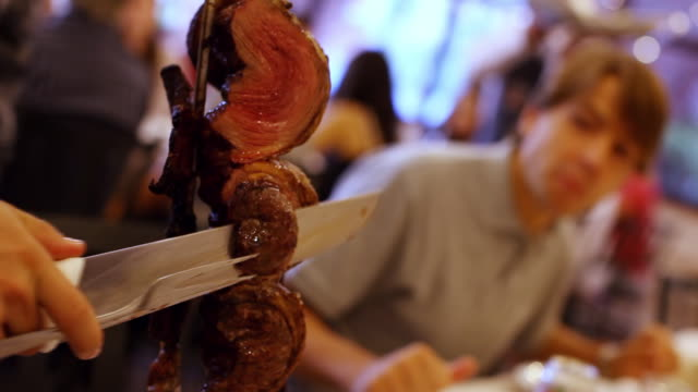 MS Shotr of Chussascaria, waiter slicing tasty meat from skewer / Curitiba, Brazil