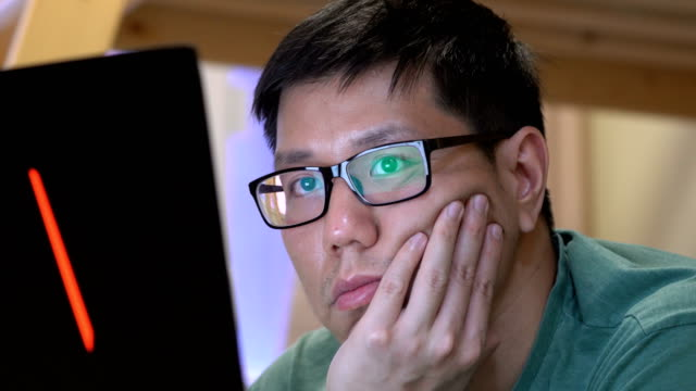 2 ショットのアジア男取得退屈ソーシャル メディアにノートブック コンピューターを使用している間 - 憂鬱点の映像素材/bロール