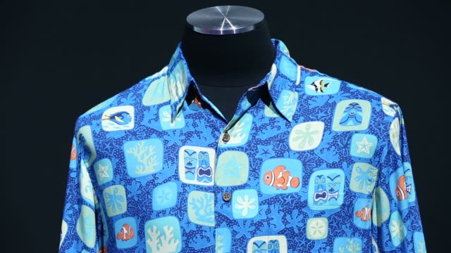Shots focus on a wall lined with shirts from the John Lasseter Studio Collection at the D23 Expo 2015 in Anaheim California US on Friday Aug 14 2015...