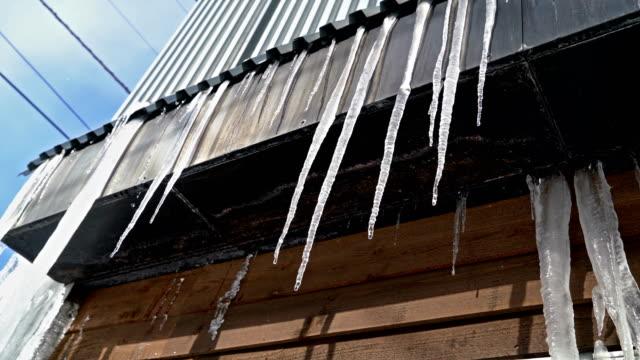 vídeos de stock, filmes e b-roll de 2 tiros icicle derretimento dos telhados e escorre para baixo em dia ensolarado - pingente de gelo