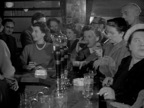 shots inside the busy york minster pub in soho patrons crowd around the bar smoking drinking and socialising 1954 - yorkshire england stock videos & royalty-free footage