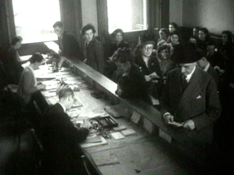 shots inside the ministry of food building a woman collects a ration book from an official sitting behind a desk 1954 - food stamps stock videos & royalty-free footage
