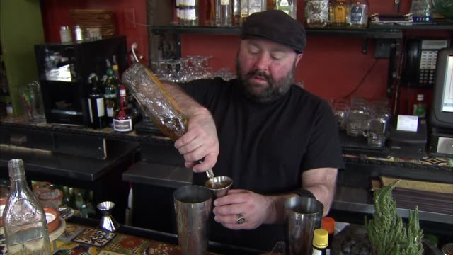 Shots of a bartender making two Mexican style drinks at a Mexican Restaurant in Brooklyn A tight shot of a bartender squeezing a thick brown liquid...