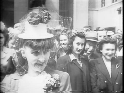 Shots of a crowd on 5th Avenue in New York waiting for the Easter parade / a uniformed soldier and his wife waiting in the crowd / a woman wearing a...