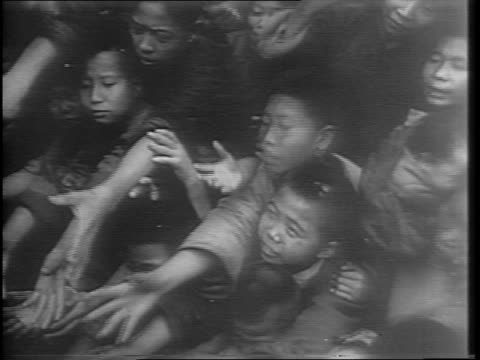 Shots of a Japanese regiment marching down a street with rifles and bayonets / High angle and close up shots of a mass of starving Chinese civilians...