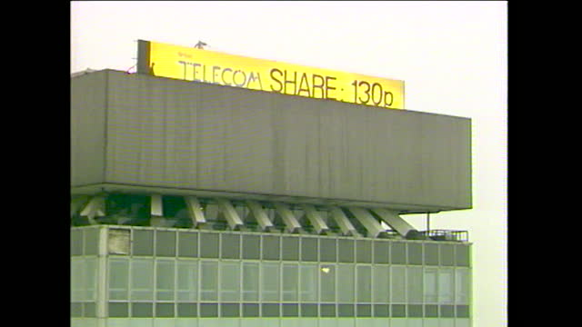 shots of a man unrolling a sign on the top of a building in the city of london announcing the british telecom share price when it was privatised in... - rolling stock videos & royalty-free footage