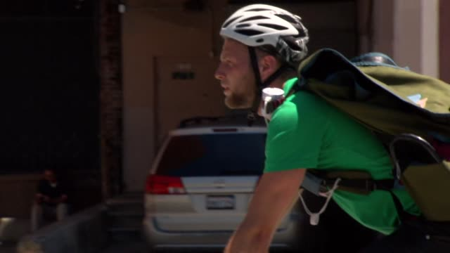 shots of a white male task rabbit in san francisco california on june 5 a medium shot of a white male riding a bike while on a task rabbit delivery a... - helm stock-videos und b-roll-filmmaterial