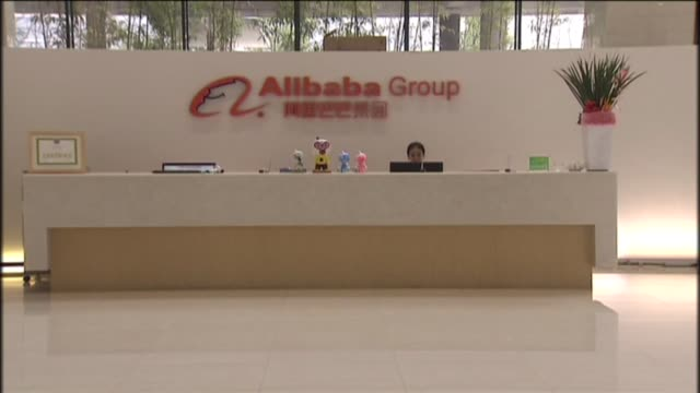 Shots of an orange Alibaba Group sign hanging above the reception desk in the lobby of their headquarters in China A receptionist answers phones...