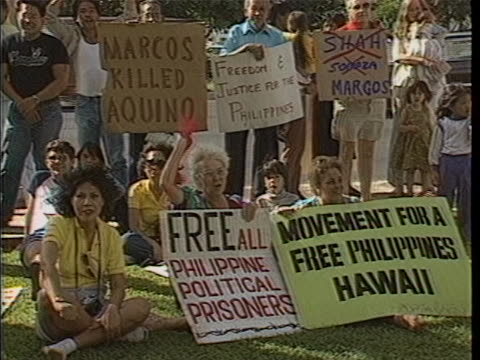 """vídeos de stock e filmes b-roll de shots of anti-marcos demonstrators sitting on the grass and lining the street carrying signs that read """"free philippine political prisoners"""" and... - aloha"""
