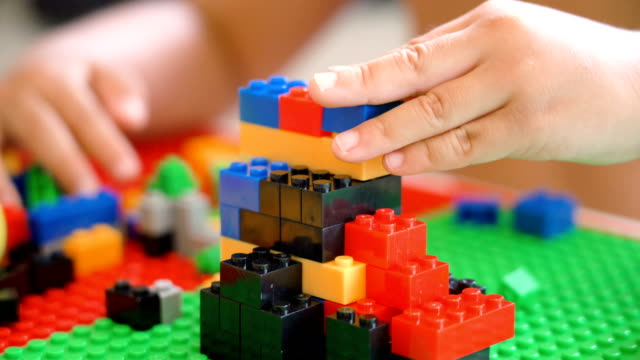 cs 2 shots of boy hand playing plastic blocks. - toy block stock videos and b-roll footage