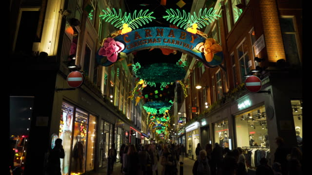 Shots of Carnaby Street with carnival style Christmas lights at night