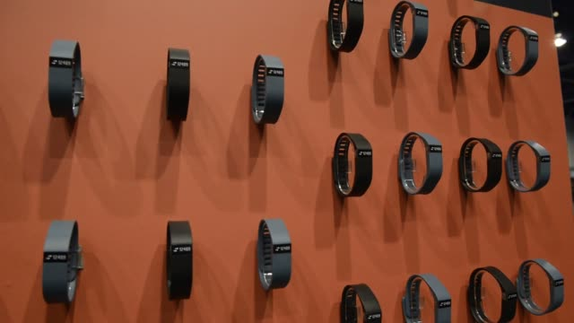 vídeos de stock, filmes e b-roll de shots of colorful smart watches at the consumer electronics show in las vegas nevada, an orange wall displays black smart watches, an attendee tries... - smart