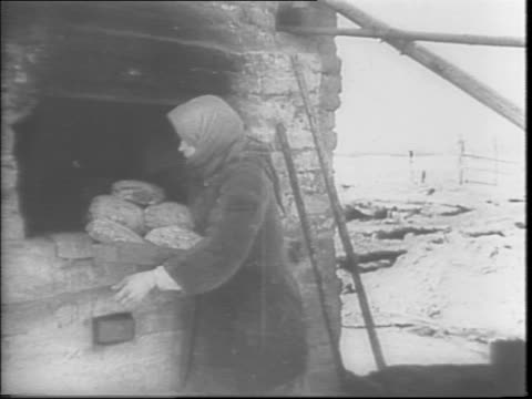 shots of dead russian soldiers / women peasants gathering flour rations in burlap bags / baking bread loaves in outdoor stone ovens / women with... - 1943 stock-videos und b-roll-filmmaterial