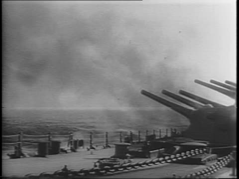 shots of explosions on the islands in the distance with black smoke billowing among the palm trees / shots of cannon barrels being fired from ships /... - artiglieria video stock e b–roll