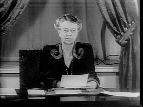 Shots of First Lady Eleanor Roosevelt wearing Red Cross uniform walking through hospital with rows of beds and wounded soldiers / shots of Roosevelt...